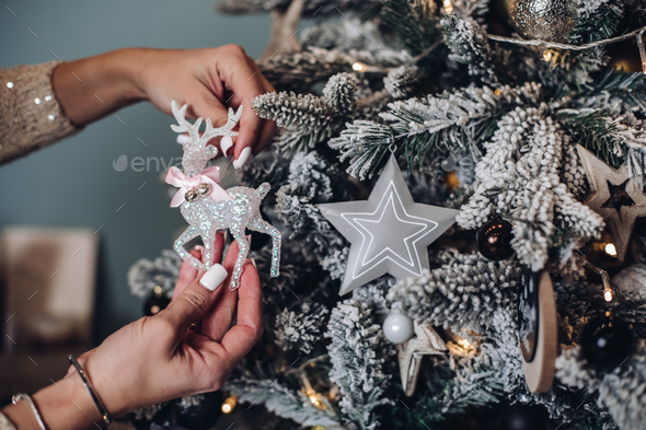 Woman placing Christmas toy on the tree - Stock Photo - Images