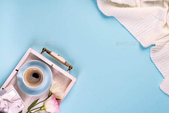 Having a cup of coffee , flowers eustoma and gift box on blanket on a blue background, flat lay copy - Stock Photo - Images