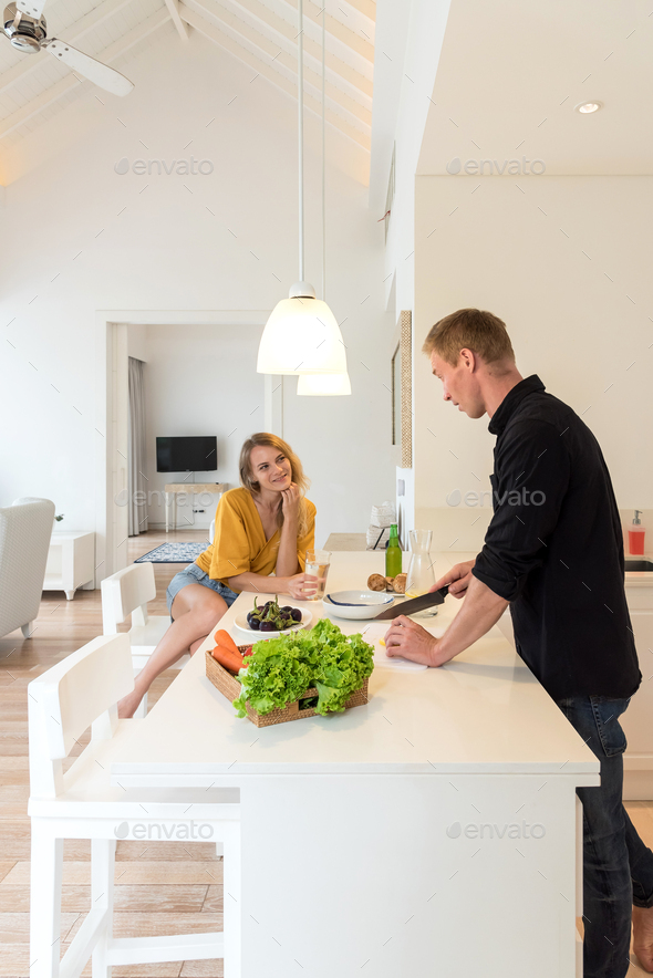 Couple making lunch on a withe kitchen at home - Stock Photo - Images