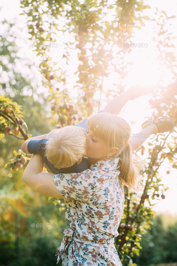 Young Woman Mother Hugging And Kissing Her Baby Son In Sunny Garden. Outdoor Summer Portrait - Stock Photo - Images