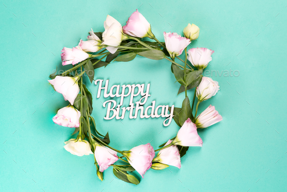 Birthday card. Wreath made of pink flowers eustoma on blue background. Flat lay, copy space - Stock Photo - Images