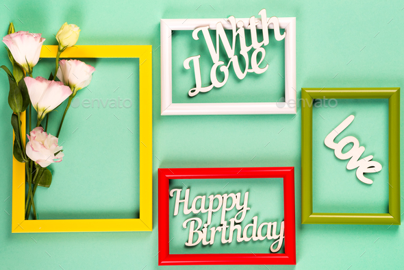 Colorful picture or photo frames with flowers and letters on a green paper background. Copy space - Stock Photo - Images