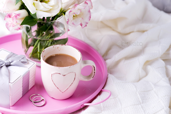 A tray with a cup of coffee, gift box, flowers and rings on the bed. Valentine's Day Wedding - Stock Photo - Images