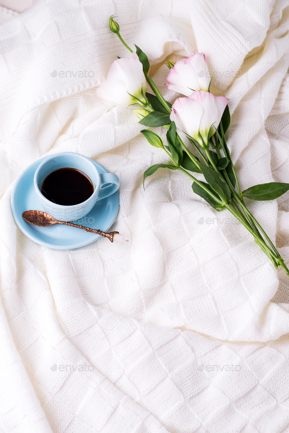 Having a cup of coffee with chocolate, flowers eustoma on blanket in bed. Holiday concept - Stock Photo - Images