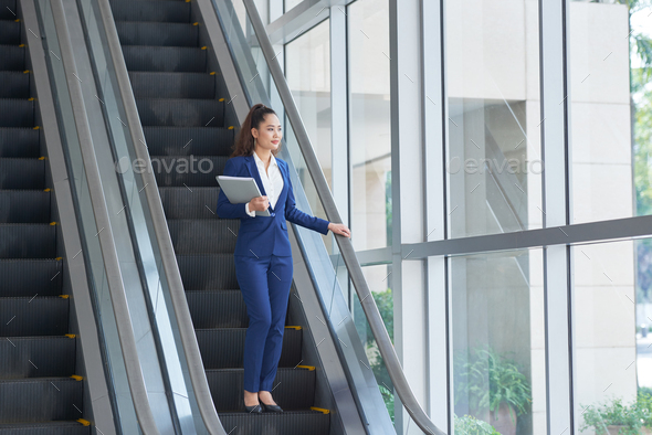 Business woman on escalator - Stock Photo - Images