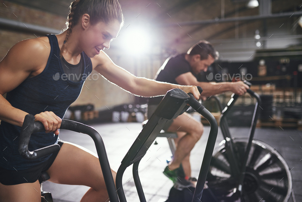 Two young people training toughly on simulators - Stock Photo - Images