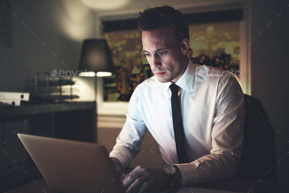Thoughtful man working at laptop in office - Stock Photo - Images