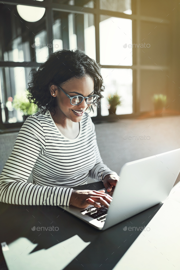 Smiling young African woman working with a laptop - Stock Photo - Images