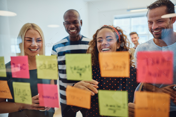 Laughing work colleagues brainstorming together in an office - Stock Photo - Images