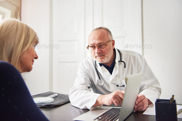 Medic explaining diagnosis to woman pointing at laptop - Stock Photo - Images