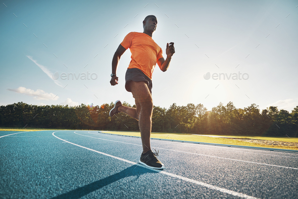 Dedicated young athlete running alone on a race track - Stock Photo - Images