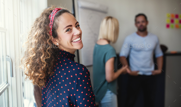 Smiling designer looking over her shoulder during a meeting - Stock Photo - Images