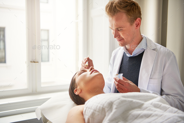 Young beautician putting mask on woman in salon - Stock Photo - Images