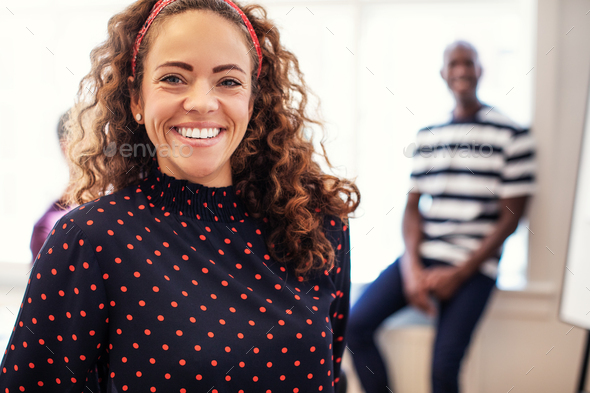 Smiling female designer standing in a modern office - Stock Photo - Images