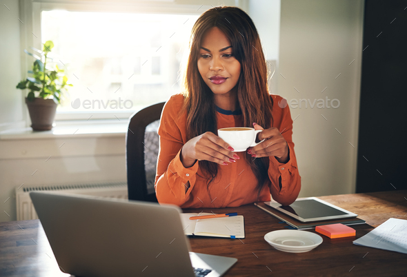 Young female entrepreneur drinking a coffee in her home office - Stock Photo - Images