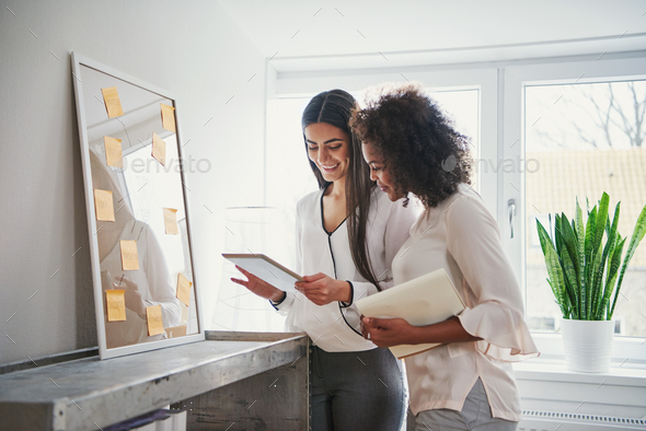 Two pretty cheerful multiracial designers browsing tablet - Stock Photo - Images