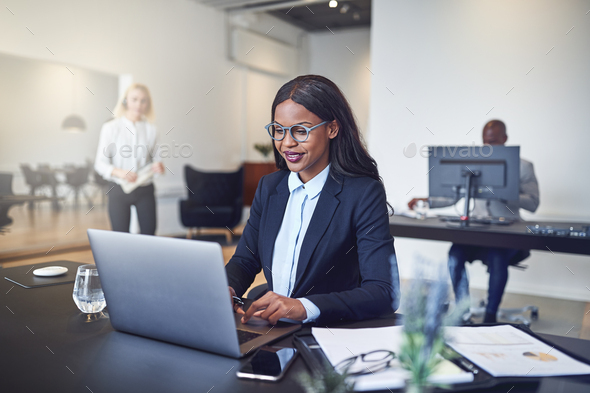 Smiling African American businesswoman sitting at work using a laptop - Stock Photo - Images
