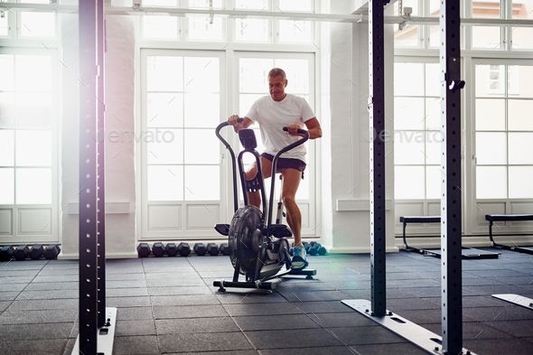 Fit mature man in sportswear riding a gym stationary bike - Stock Photo - Images