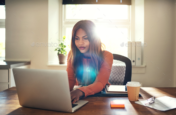 Young woman working on a laptop in her home office - Stock Photo - Images