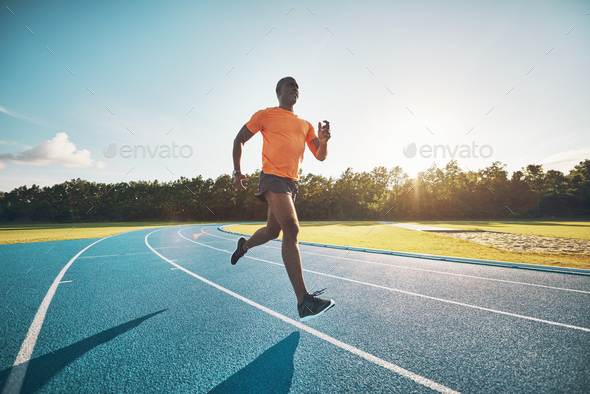 Focused young athlete sprinting alone down a running track - Stock Photo - Images
