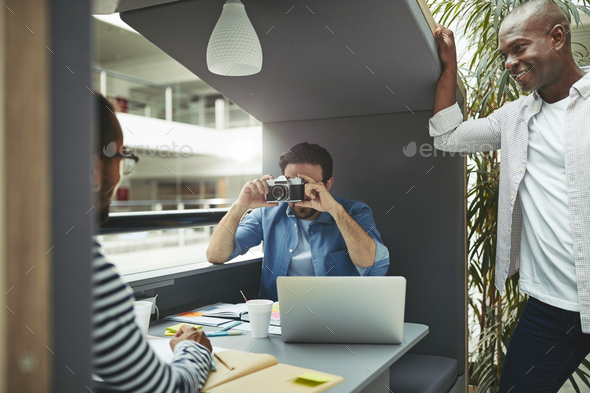 Designer taking a colleague's photo in an office meeting pod - Stock Photo - Images