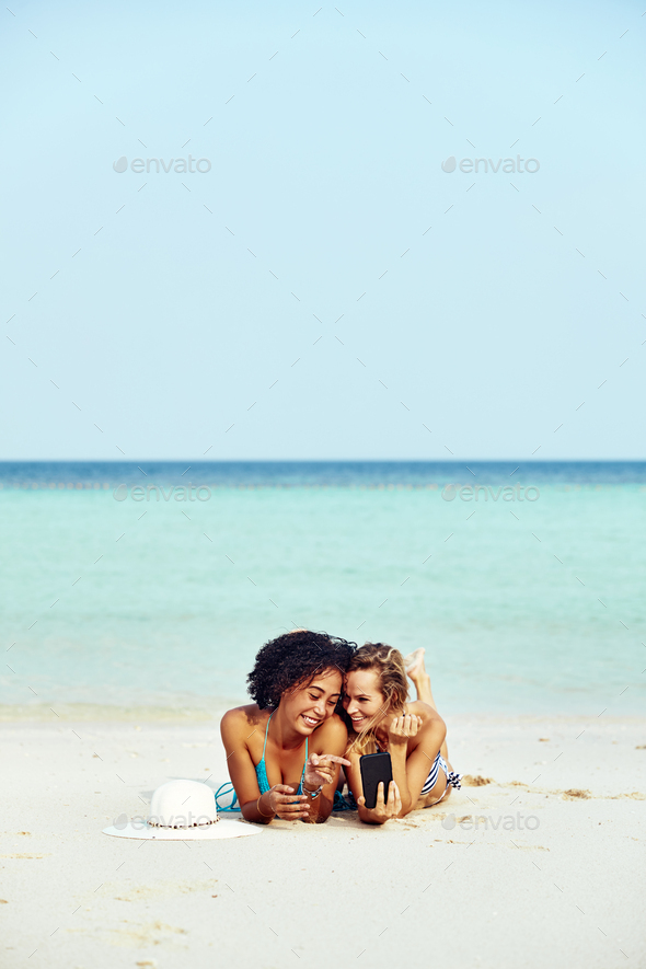 Two suntanning friends looking at cellphone photos on a beach - Stock Photo - Images