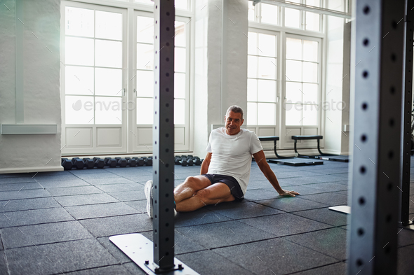 Smiling senior man sitting on the floor of a gym - Stock Photo - Images
