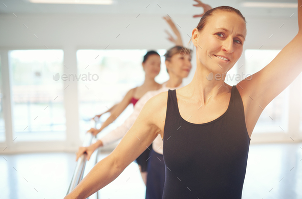 Adult woman looking at camera doing gymnastics in ballet class - Stock Photo - Images