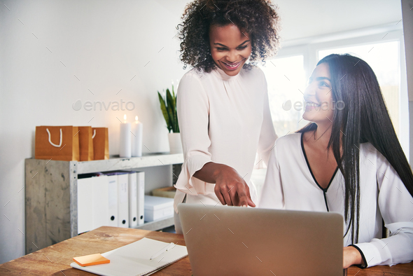 Two contemporary designers working together at laptop - Stock Photo - Images