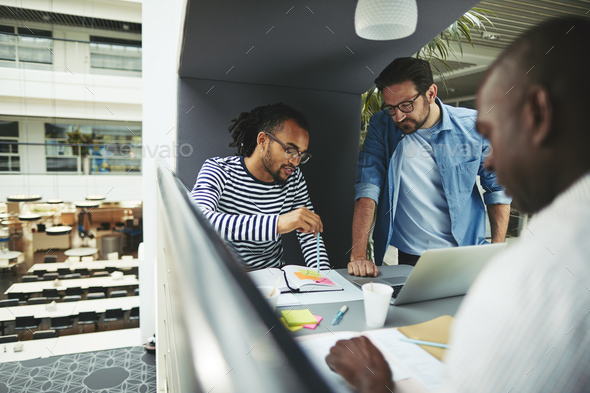 Businessmen discussing work while working in an office pod - Stock Photo - Images