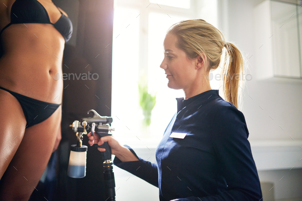 Woman spraying client with airbrush during spraytan session - Stock Photo - Images