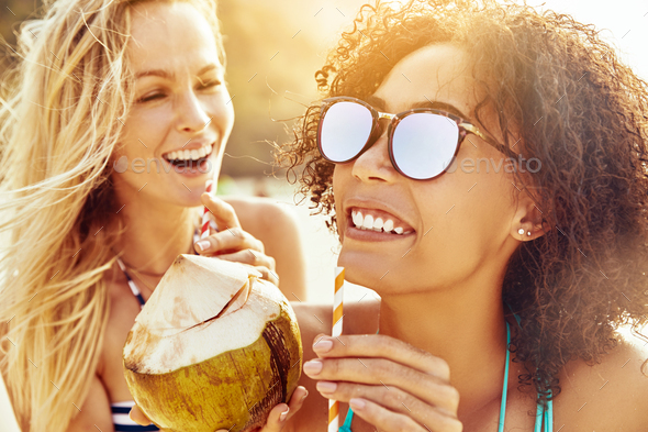 Laughing female friends sipping from coconuts on a sandy beach - Stock Photo - Images