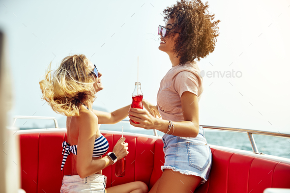Two smiling young women enjoying drinks together on a boat - Stock Photo - Images
