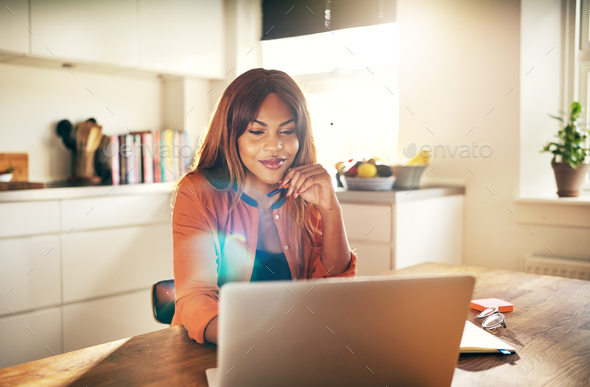 Successful female entrepreneur working on a laptop in her kitchen - Stock Photo - Images
