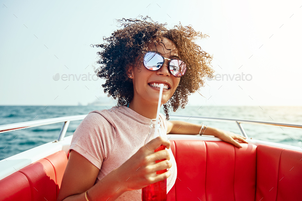 Smiling woman sipping on a drink while out sailing - Stock Photo - Images
