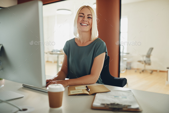 Young businesswoman laughing while working at her office desk - Stock Photo - Images