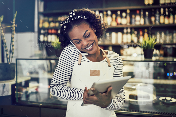 Smiling young African entrepreneur taking reservations in her cafe - Stock Photo - Images