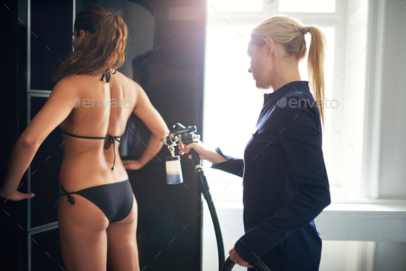 Beauty professional providing spraytan procedure to client - Stock Photo - Images