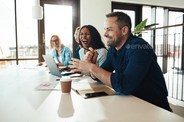 Businessman laughing with a group of office colleagues at work - Stock Photo - Images