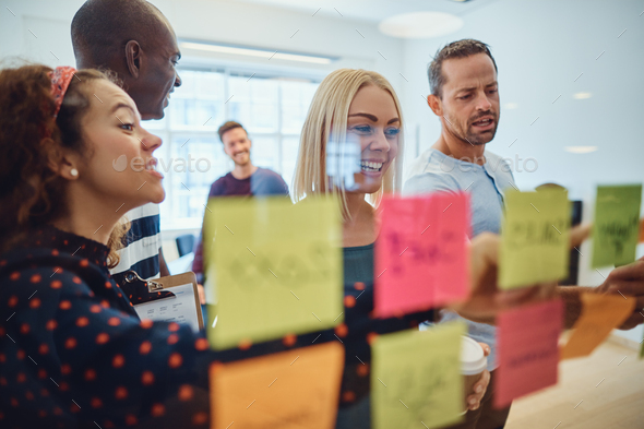 Smiling team of designers brainstorming together on an office wall - Stock Photo - Images