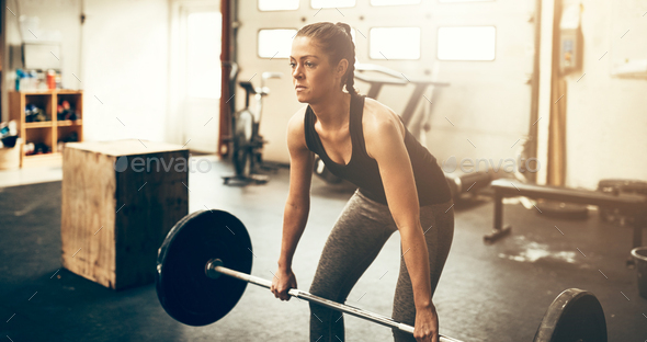 Fit young woman lifting weights during a workout - Stock Photo - Images