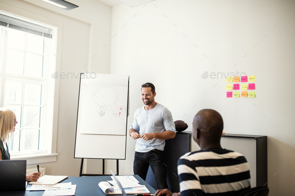 Smiling manager talking with staff during a whiteboard presentation - Stock Photo - Images