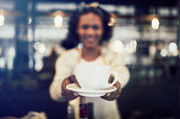 Cafe barista offering up a cup of cfresh coffee - Stock Photo - Images