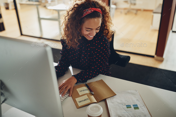 Laughing young businesswoman reading notes and working on a computer - Stock Photo - Images