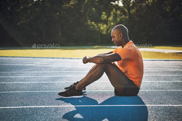 Focused young runner sitting alone on a track - Stock Photo - Images