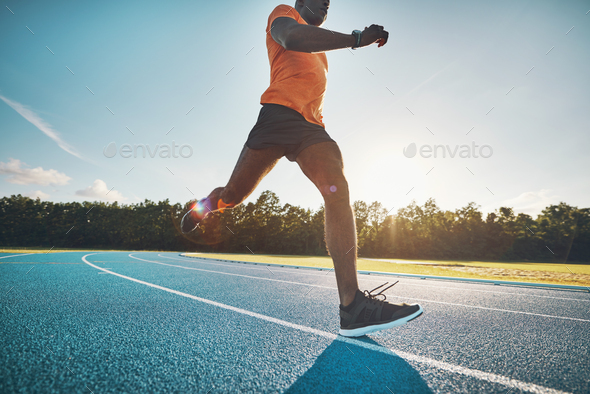Fit young African athlete running alone on a track - Stock Photo - Images