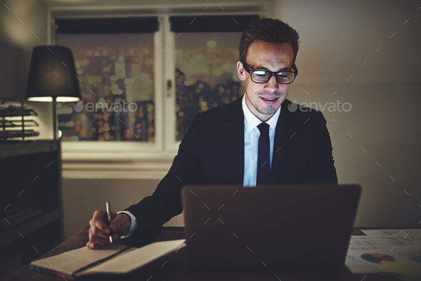 Smiling businessman working on laptop - Stock Photo - Images