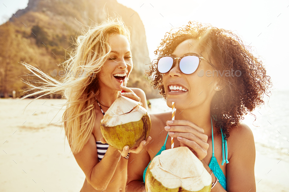 Laughing friends in bikinis drinking from coconuts on a beach - Stock Photo - Images