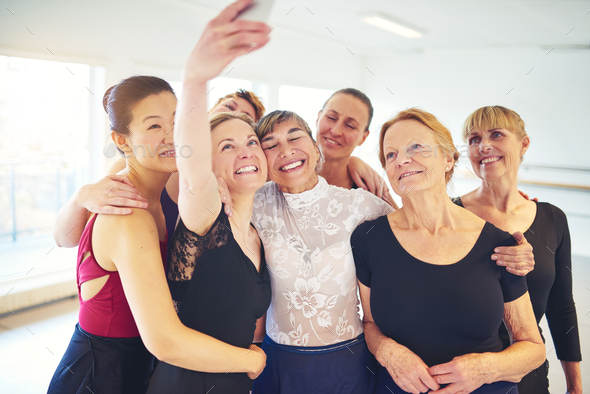 Smiling group of friends taking selfies in a dance studio - Stock Photo - Images