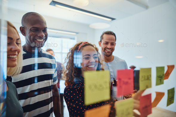 Smiling office colleagues brainstorming together with sticky notes - Stock Photo - Images